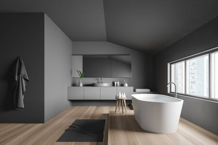 Side view of minimalistic bathroom with dark grey walls, wooden floor, comfortable white bathtub near window and round sink with big mirror. 3d rendering