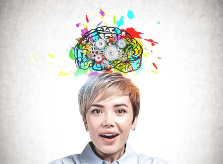 Astonished young businesswoman standing near concrete wall with colorful brain sketch with gears drawn on it. Concept of brainstorming
