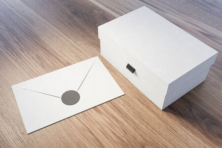 Closed white gift box and white envelope lying on wooden table. Concept of holidays and celebration. 3d rendering