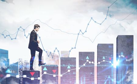 Confident young businessman climbing bar chart in modern city with double exposure of digital graphs. Concept of trading and good career. Toned image Archivio Fotografico - 133855383