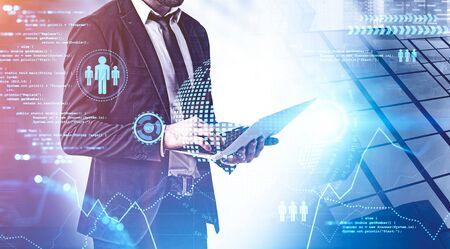 Hombre de negocios joven irreconocible que trabaja con la computadora portátil en la ciudad con doble exposición de la interfaz de big data. Imagen tonificada