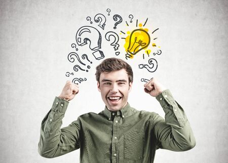 Happy young man in green shirt screaming with joy standing near concrete wall with question marks and light bulb drawn on it. Concept of bright idea