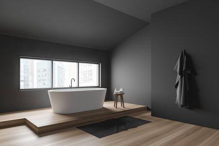 Corner of minimalistic bathroom with dark grey walls, wooden floor, comfortable white bathtub under window and chair with towels. 3d rendering Stock fotó