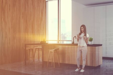 Woman with phone and coffee standing in modern kitchen corner with white and wooden walls, concrete floor and wooden bar with stools. Toned image double exposure