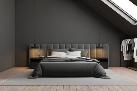 Interior of attic bedroom with gray walls, wooden floor, grey king size bed with square bedside tables and clothes on hangers. 3d rendering