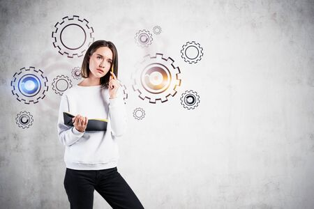 Thoughtful young woman in casual clothes with notebook standing near concrete wall with gears drawn on it. Concept of brainstorming. Mock up