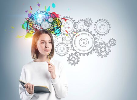 Thoughtful young woman in casual clothes with notebook standing near gray wall with colorful brain sketch with gears drawn on it. Concept of brainstorming