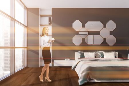 Blonde young woman standing in stylish bedroom with gray walls, wooden floor and comfortable king size bed with mirrors above it. Toned image