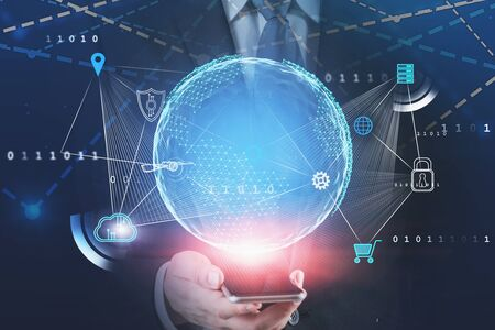Front view of businessman looking at his smartphone with double exposure of big data interface and planet hologram. Toned image