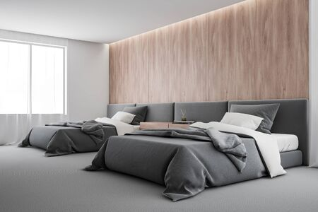 Corner of comfortable bedroom or hotel suite with wooden and white walls, carpeted floor and two beds with wooden bedside table between them. 3d rendering