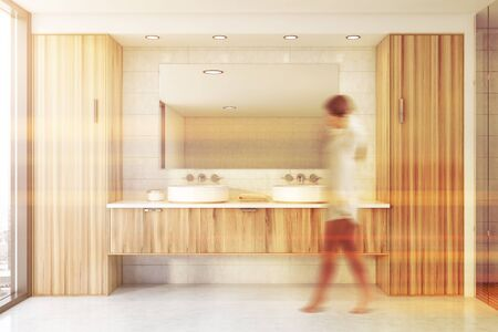 Blurry young woman walking in spacious bathroom with white tile walls, concrete floor and comfortable double sink standing on wooden countertop. Toned image