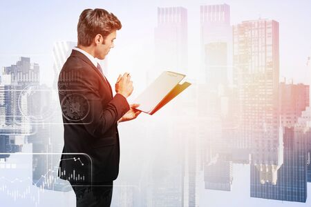 Serious young businessman standing with clipboard in city with double exposure of blurry infographics interface. Concept of statistics and data. Toned image