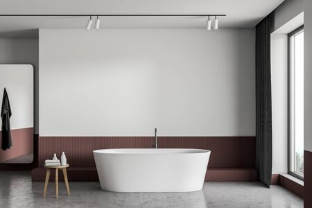 Interior of minimalistic bathroom with white and red walls, concrete floor, comfortable bathtub and big window with curtains. 3d rendering Foto de archivo