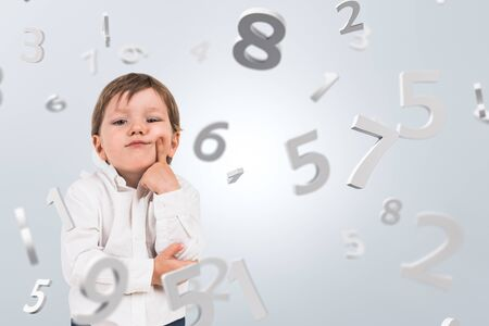 Smart little preschool boy in white shirt standing over white background with falling numbers. Concept of education and math