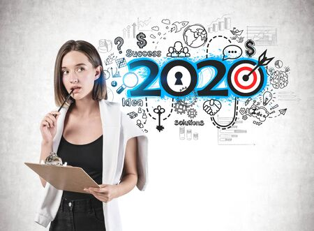 Pensive young woman in casual clothes with clipboard standing near concrete wall with colorful 2020 business plan sketch drawn on it. Concept of new year goals and resolutions.