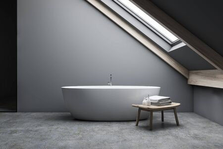 Interior of minimalistic attic bathroom with grey walls, concrete floor and comfortable bathtub standing under window in the roof with bench beside it. 3d rendering