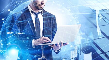 Unrecognizable bearded businessman working with laptop in modern city with double exposure of blurry network interface. Concept of coding and internet connection. Toned image Stock Photo