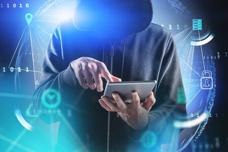Unrecognizable hacker working with tablet over blue background with double exposure of planet hologram and GUI. Concept of data protection and cyber crime. Toned blurry image 写真素材