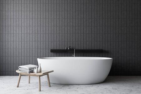 Minimalistic bathroom interior with grey tile walls, stone floor, comfortable white bathtub with black shelf and chair with towels. Concept of spa. 3d rendering
