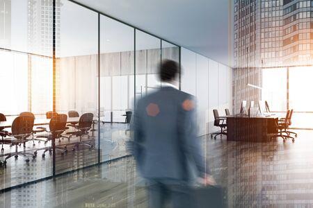 Verschwommener Geschäftsmann, der ein modernes Open-Space-Büro mit weißen und hölzernen Wänden und einen komfortablen Tagungsraum mit einem Konferenztisch aus Holz betritt. Doppelbelichtung des getönten Bildes