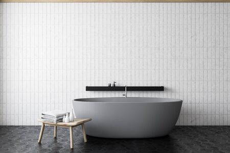 Minimalistic bathroom interior with white tile walls, hexagonal pattern floor, comfortable grey bathtub with black shelf and chair with towels. Concept of spa. 3d rendering 스톡 콘텐츠