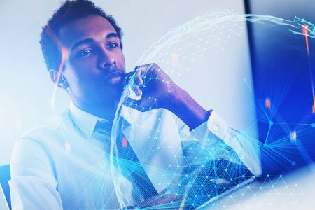 Concentrated young African American businessman looking at laptop in office with double exposure of planet hologram and blurry network interface. Concept of hi tech in business. Toned image Stock Photo