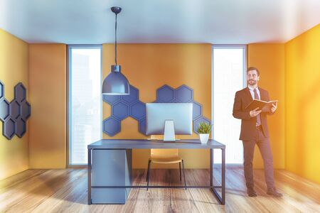 Young businessman with book standing in modern CEO office with yellow hexagonal pattern walls, wooden floor and gray computer table. Concept of management. Toned image