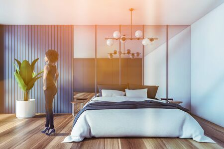 African American woman standing in stylish bedroom with blue and white walls, wooden floor, comfortable master bed and big mirror. Toned image