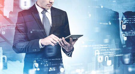 Nicht erkennbarer Geschäftsmann, der mit Tablet-Computern in der Stadt arbeitet, mit Doppelbelichtung der verschwommenen Cybersicherheitsschnittstelle. Konzept des Datenschutzes. Getöntes Bild Standard-Bild