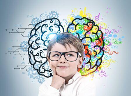 Entzückender lächelnder kleiner Junge mit Brille, der in der Nähe der grauen Wand steht, mit bunter Skizze des linken und rechten Gehirns. Konzept des Brainstormings und der Bildung. Standard-Bild