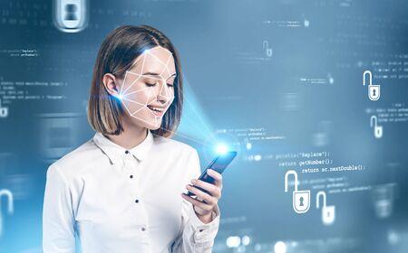 Souriante jeune femme en vêtements formels utilisant un smartphone avec technologie de reconnaissance faciale sur fond bleu flou. Concept d'authentification biométrique et de cybersécurité. Image tonique double exposition
