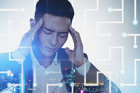 Young stressed Asian businessman standing in night city with double exposure of digital maze. Concept of being tired of technology and overwork. Toned image