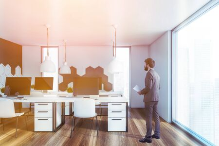 Young businessman with documents standing in modern office with white and gray walls with hexagonal pattern, wooden floor and row of computer desks. Toned image