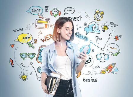 Cheerful teen girl in casual clothes with stack of books and smartphone standing near gray wall with creative social media sketch drawn on it.