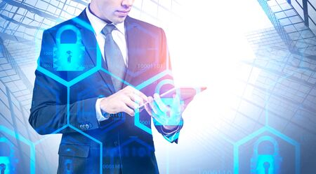Unrecognizable engineer working with tablet computer in city with double exposure of blurry cyber security interface. Concept of data protection. Toned image
