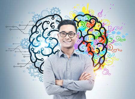 Confident smiling Asian businessman with glasses standing with crossed arms near gray wall with colorful left and right brain sketch. Concept of brainstorming and education. Stock Photo