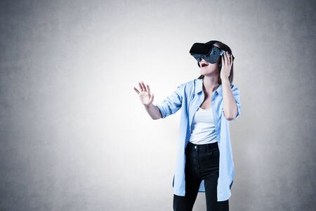 Portrait of happy young woman in casual clothes gesturing and having pleasant virtual reality experience over concrete wall background. Concept of hi tech and entertainment. Mock up