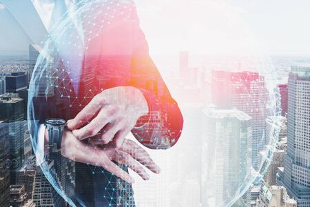 Close up of businessman checking his watch in city with double exposure of network interface. Concept of internet connection. Toned image