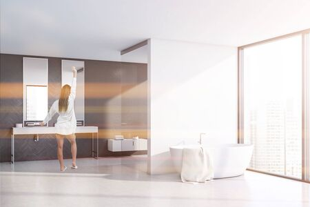 Young woman in nightgown stretching in sunlit bathroom with white and grey wooden walls, concrete floor, double sink and comfortable bathtub. Toned image Zdjęcie Seryjne