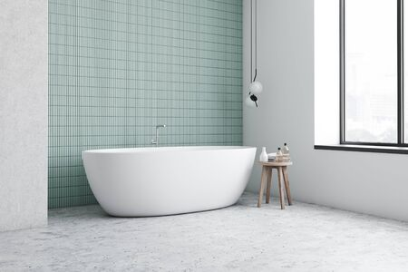 Corner of minimalistic bathroom with blue tile and white walls, stone floor, comfortable white bathtub and chair with towels and beauty products. 3d rendering
