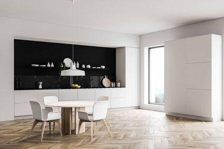 Ecke der Luxusküche mit weißen und schwarzen Marmorwänden, Holzboden, weißen Arbeitsplatten, großem Schrank und rundem Esstisch mit Stühlen. 3D-Rendering Standard-Bild