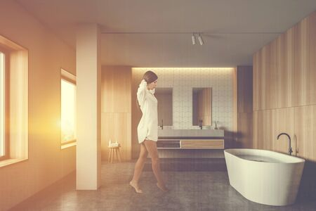 Woman walking in sunlit bathroom with white tile and wooden walls, comfortable bathtub with water and double sink with mirrors. Toned image double exposure