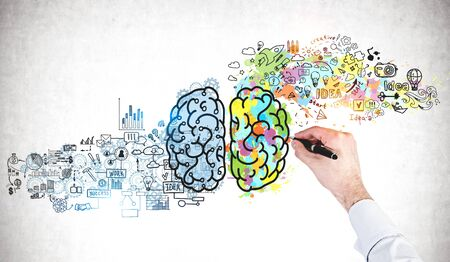Businessman hand drawing colorful brain sketch on concrete wall. Concept of creative thinking and brainstorming