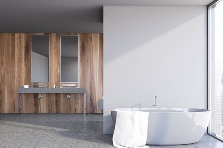 Interior of stylish bathroom with gray and wooden walls, concrete floor, double sink standing on gray countertop with two mirrors and comfortable grey bathtub. 3d rendering
