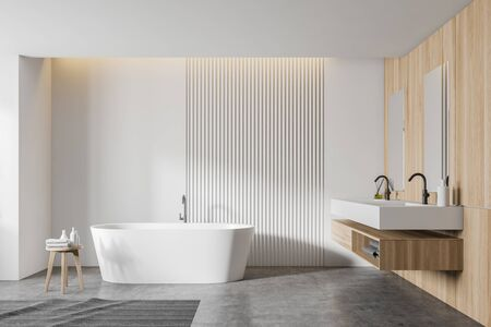 Interior of modern bathroom with white and wooden walls, concrete floor, comfortable white bathtub and double sink with wooden shelf. 3d rendering Zdjęcie Seryjne