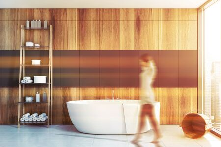 Blurry young woman walking in stylish sunlit bathroom with gray and wooden walls, tiled floor, comfortable white bathtub and shelves with cosmetic products. Concept of spa. Tone image Zdjęcie Seryjne