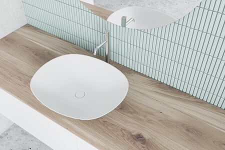 Top view of sink standing on wooden countertop in modern bathroom with blue tiled and concrete walls and round mirror. 3d rendering