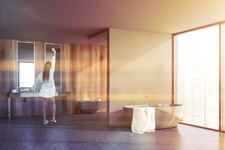 Young woman in nightgown stretching in sunlit bathroom with gray and wooden walls, concrete floor, double sink and comfortable bathtub. Toned image