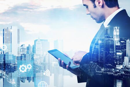 Vista laterale dell'uomo d'affari che utilizza il computer tablet nella città notturna con doppia esposizione dell'interfaccia big data. Immagine tonica