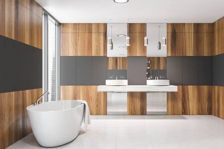 Interior of stylish bathroom with gray and wooden walls, white tiled floor, comfortable white bathtub and double sink with two mirrors. 3d rendering